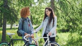 Nätta flickor som moderna studenter har konversation parkerar in, samtal, och skratta att rymma cyklar med härlig gräsplan stock video
