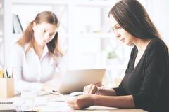Nätta kvinnlig som gör skrivbordsarbete Fotografering för Bildbyråer