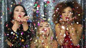 Nätta kvinnor som blåser på konfettier lager videofilmer