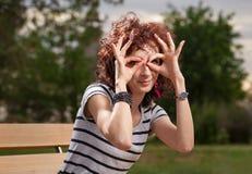 Nätta lockiga haired kvinnor gör exponeringsglas vid hennes händer Arkivbilder