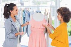 Nätta modeformgivare som justerar en klänning Arkivbild