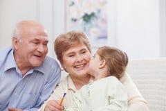 Nätta morföräldrar tar omsorg av barnet Arkivbilder