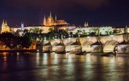 Nätta nattetidbelysningar av den Prague slotten, Charles Bridge och St Vitus Cathedral reflekterade i den Vltava floden Fotografering för Bildbyråer