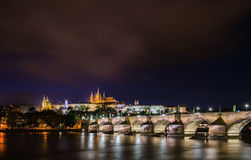 Nätta nattetidbelysningar av den Prague slotten, Charles Bridge och St Vitus Cathedral reflekterade i den Vltava floden Arkivfoto