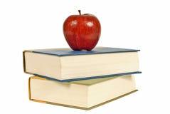 Nätta röda Apple på bunt av böcker Arkivfoto