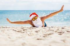 Nätta Santa Claus i solglasögon på stranden med havsikter Arkivfoto