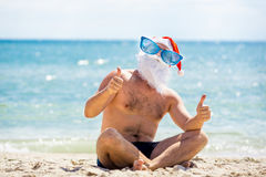 Nätta Santa Claus i solglasögon på stranden med havsikter Royaltyfri Foto