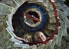 Nätta små flickor på stenspiraltrappuppgång royaltyfria foton