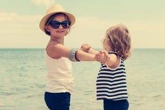 Nätta små flickor (systrar) som dansar på stranden Arkivfoto