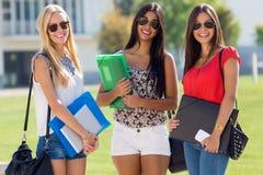 Nätta studentflickor som har gyckel på universitetsområdet Arkivbilder