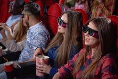 Nätta tonåringar som tycker om komedi i bio royaltyfri foto