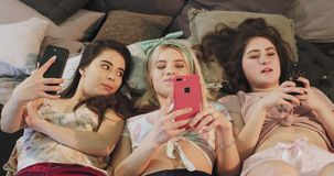 Nätta tonåringdamer i kläder för en homewear genom att använda en smartphone, medan lägga ner på sängen, äta som är tuggummi och arkivfilmer