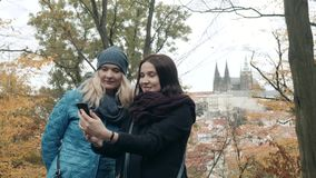 Nätta två och lycklig ung kvinna som gör Selife med mobiltelefonen i Autumn Park Bästa vän gör selfie arkivfilmer