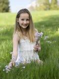 Nätta ung flickaplockningvildblommor Arkivfoto