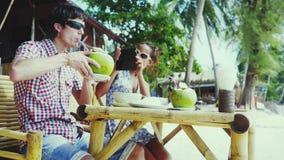 Nätta unga par i solglasögon som sitter på ett trevligt kafé vid stranden Flickan tar en bild hennes pojkvän med mobilen stock video