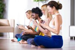 Nätta unga sportiga kvinnor som hemma använder mobiltelefonen efter yogaperiod arkivbild