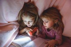 Nätta ungar som läser berättelse under täcket royaltyfria bilder