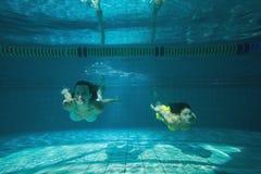 Nätta vänner som ler och simmar som är undervattens- Arkivbild