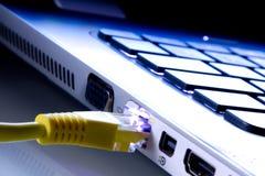 Nätverkskabel pluggade in bärbara datorn Arkivbild