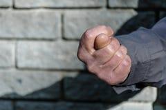 Näve med en tumme mellan indexet och långfingrarna, fikonträdtecken Gestmäns hand av negationen Begrepp av kasseringen closeup arkivfoto