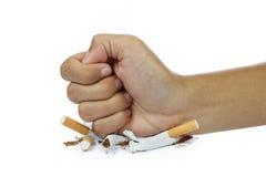 näve som bryter cigarettstoppet som röker begrepp på vit Arkivfoton
