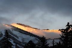 Nå en höjdpunkt solen, på det snöig berget royaltyfria foton