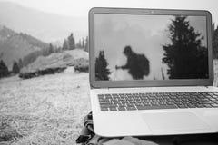 Någon använder bärbara datorn avlägset på berget Royaltyfri Foto