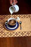 Någon häller något mjölkar ut ur mjölkar tillbringaren in i en kopp kaffe arkivfoto