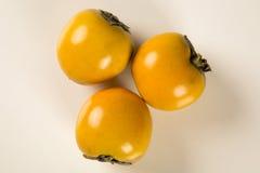 Någon kaki bär frukt på vit bakgrund Fotografering för Bildbyråer