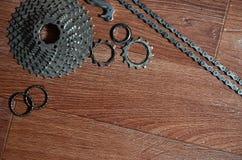 Någon sammansättning av en cykelkedja, flera tandhjul och annat Arkivbild