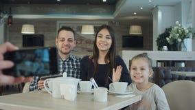 Någon som tar fotoet på mobiltelefonen av den unga lyckliga familjen i kafé fotografering för bildbyråer