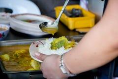 Någon sveper fisken i gul curry på vita ris i en platta arkivfoto
