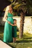 Något liknande fostrar den lika dottern härlig gravid kvinna med hennes barn arkivbild