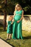 Något liknande fostrar den lika dottern härlig gravid kvinna med hennes barn royaltyfri bild