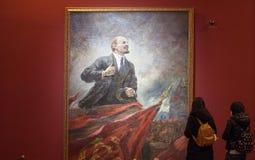Något ungt kinesiskt framme av en målning av Lenin Royaltyfri Foto