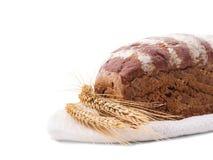 Några öron av vete nära det svarta brödet på en handduk Royaltyfri Foto