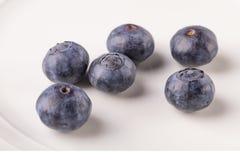 Några blåbär på en vit plattanärbild arkivbilder