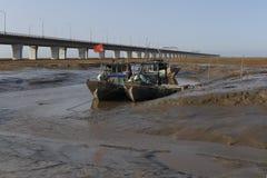 Några förtöjde den enkla fiskebåten i våtmark som hängdes med den kinesiska flaggan Arkivbild