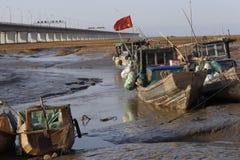 Några förtöjde den enkla fiskebåten i våtmark som hängdes med den kinesiska flaggan Arkivbilder