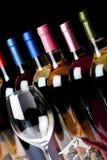Några flaskor av vin, korkskruv och ett vinexponeringsglas Fotografering för Bildbyråer
