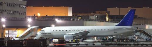 Några flygplan som stiger ombord på en flygplats på natten Arkivfoton