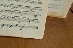 Några gamla musikböcker på en träyttersida Arkivfoton