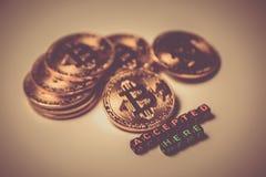 Några guld- mynt med tecknet av bitcoin och accepterade här `en för inskrift den `, Guld tonad bild Arkivbilder