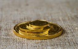 Några guld- mynt på en bakgrund av grov wood textur Arkivbild