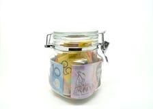 Några hållna australiensiska pengar låser i kruset. Arkivbilder