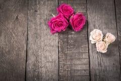 Några kräm- och rosa rosor på träbakgrund Arkivfoto