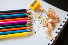 Några kulöra blyertspennor av olika färger och en vässare Royaltyfria Bilder