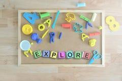 Några kulöra kubbokstäver på en svart tavla i ett klassrum som bildar ordet, UNDERSÖKER Arkivfoton