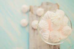 Några läckra rosa macarons i en glass krus på en vit trätabell med ett rödhakeägg slösar bakgrund tappning för stil för illustrat Royaltyfri Bild