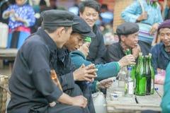 Några män för etnisk minoritet som till varandra talar, på den gamla Dong Van marknaden royaltyfri foto